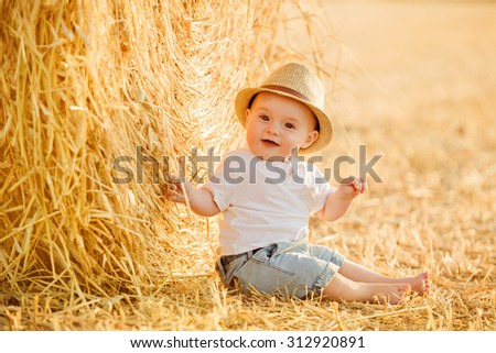 Little adorable baby boy with big brown eyes in a hat sits in a field near haystacks at sunset in the summer and smiles - stock photo