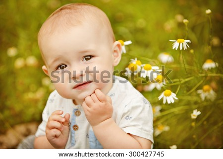 Little adorable baby boy with big eyes sitting in a field with daisies in the summer and looking up, close-up - stock photo