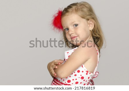 Little adorable blonde girl with a red flower in her hair smiling and having fun, toddler playing - stock photo