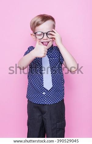 Little adorable boy in tie and glasses. School. Preschool. Fashion. Studio portrait over pink background - stock photo