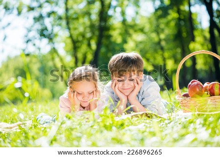 Little adorable children in park laying on grass - stock photo