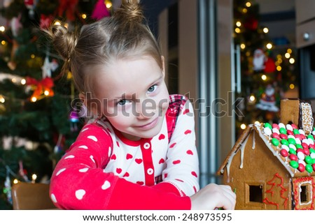Little adorable girl decorating gingerbread house for Christmas - stock photo