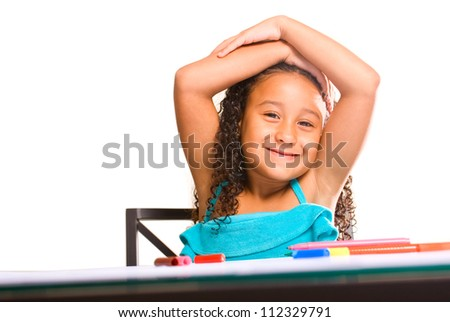 Little adorable girl drawing with markers at her desk - stock photo