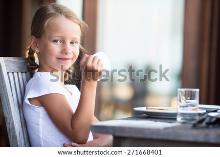 Little adorable girl drinking tea on breakfast in outdoor cafe - stock photo