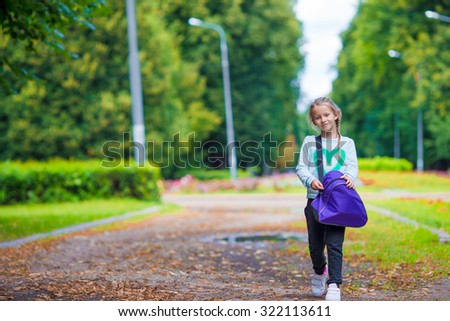 Little adorable girl going to the gym with her sports bag - stock photo