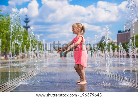 Little adorable girl have fun in street fountain at hot sunny day - stock photo