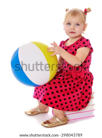 Little adorable girl in a red dress with polka dots sitting on a stack of books and holding a ball
