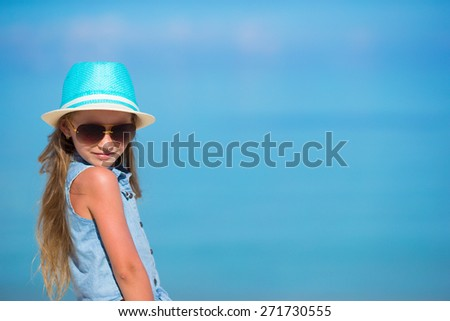 Little adorable girl in hat at beach during summer vacation - stock photo