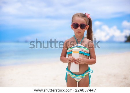 Little adorable girl in swimsuit holds suntan lotion bottle - stock photo