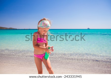 Little adorable girl in swimsuit with suntan lotion bottle - stock photo