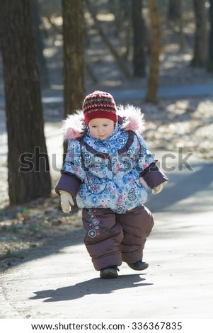 Little adorable girl is toddling without help in cold weather park  - stock photo