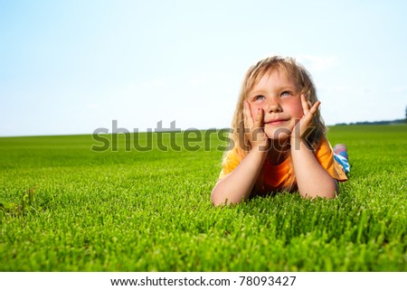 Little adorable girl lying on grass - stock photo