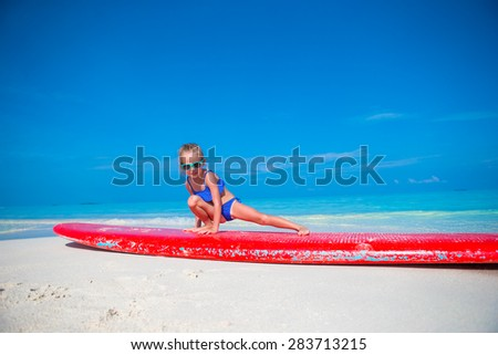 Little adorable girl on a surfboard in the turquoise sea - stock photo