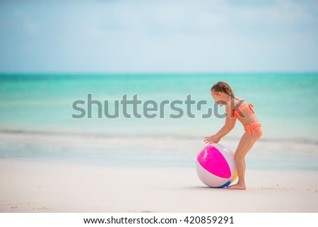 Little adorable girl playing on white beach with air ball - stock photo
