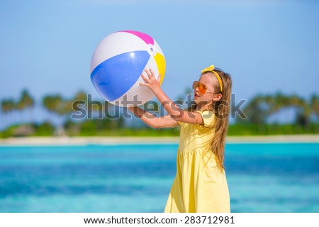Little adorable girl playing with air ball outdoor on beach - stock photo