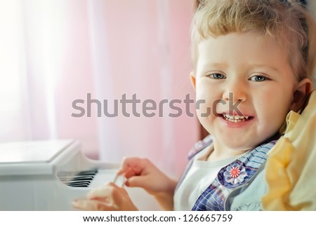Little adorable girl plays with a toy grand piano - stock photo