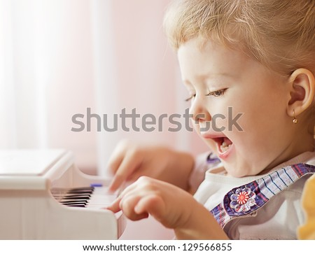 Little adorable girl plays with a toy grand piano and sings - stock photo