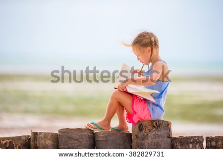 Little adorable girl reading book during tropical white beach - stock photo