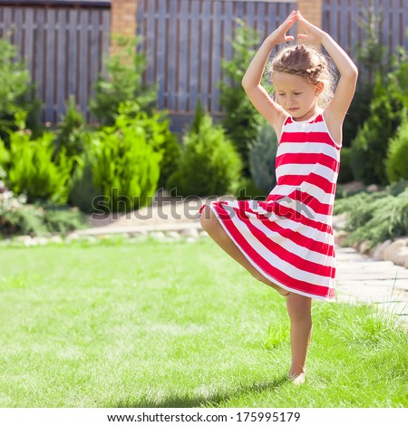 Little adorable girl standing in a yoga pose on one leg - stock photo
