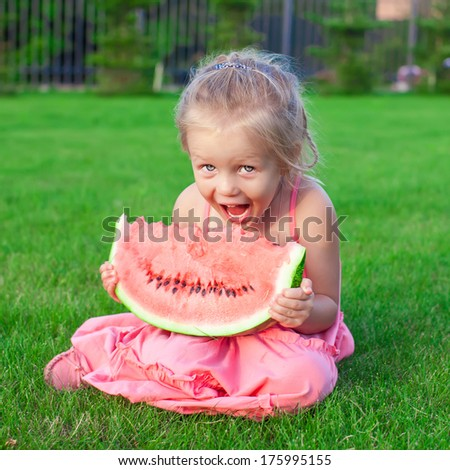 Little adorable girl with a piece of watermelon in hands - stock photo
