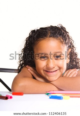 little adorable girl working at her desk smiling looking at camera - stock photo