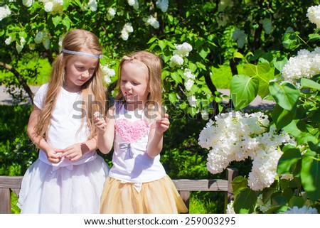 Little adorable girls at blossom trees park