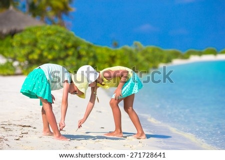 Little adorable girls drawing picture on white beach - stock photo