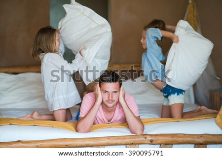 Little adorable girls fighting pillows near their dad - stock photo