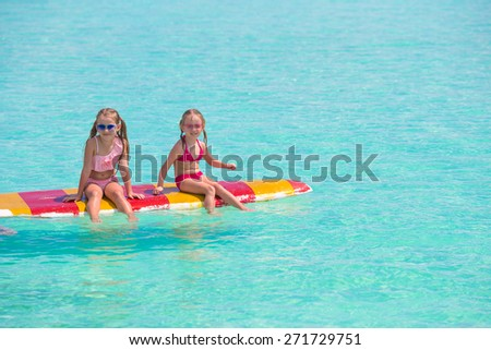 Little adorable girls on a surfboard in the turquoise sea - stock photo