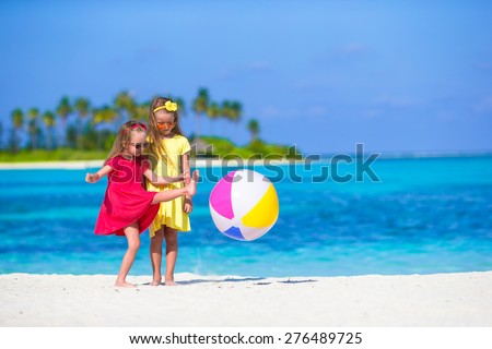 Little adorable girls playing on beach with ball - stock photo