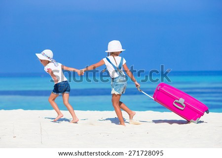 Little adorable girls with big suitcase on tropical white beach during summer vacation - stock photo