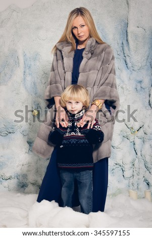 Little adorable happy boy and mom in studio with snow - stock photo