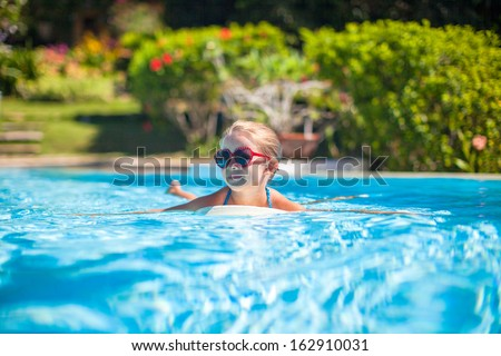 Little adorable happy girl swims in the swimming pool - stock photo