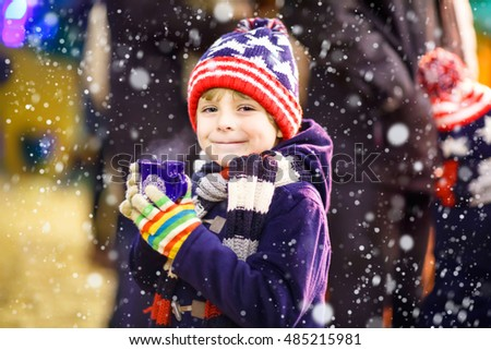 Little adorable kid boy with cup of steaming hot chocolate or children punch. Happy child on Christmas market in Germany. Traditional leisure for families on xmas
