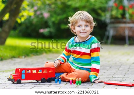 Little adorable preschool boy playing with red school bus and toys in summer garden on warm sunny day.