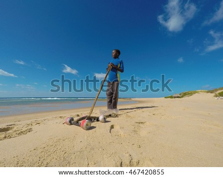 Little african boy playing in the sand with his wire car