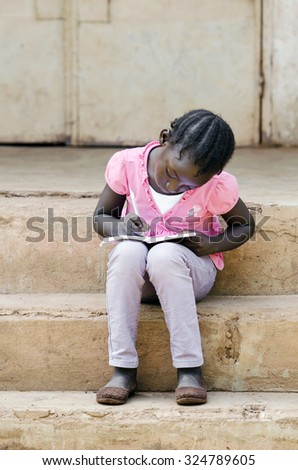 Little African ethnicity girl studying her lesson sitting on her school's stairs. Concentrating black child writing down some notes on her exercise book to do her homework for the lesson. - stock photo
