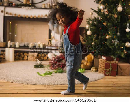 Little African Girl at Home with Christmas Interior - stock photo