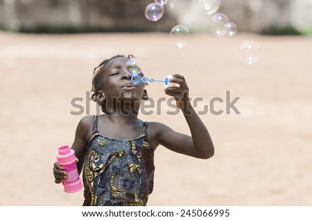 Little African Girl Having Fun Playing With Soap Bubbles - stock photo