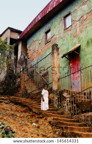 Little African girl toddler, in stairs of old, creepy concrete buildings in the city: poverty concept. - stock photo