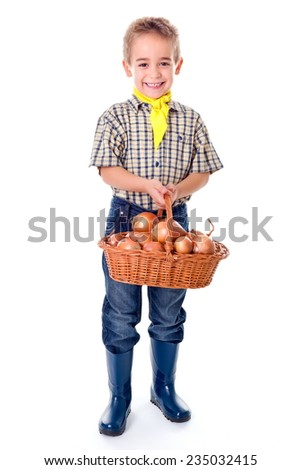 Little agriculturist boy holding big basket full with onions - stock photo