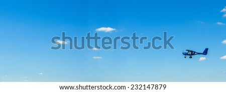 little airplane flying in the blue sky