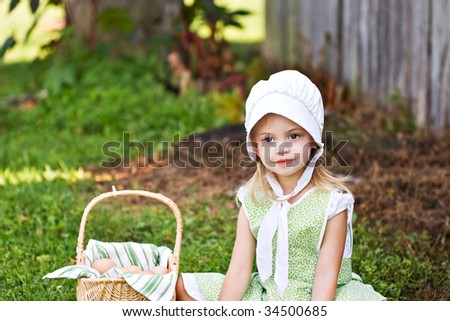 Little Amish girl gathering eggs - stock photo