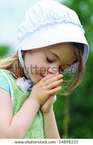 Little Amish/Mennonite child bows her head to pray. - stock photo