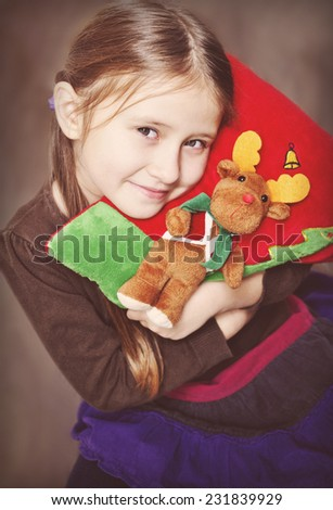 Little and decorative pillow with Christmas deer and Christmas tree. Little girl enjoys Christmas time. - stock photo