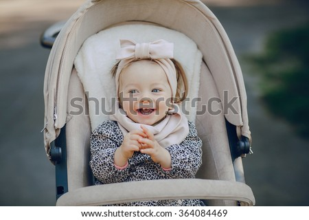 little  and very beautiful girl sitting in the pram and waiting for mom - stock photo