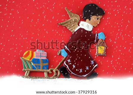 Little Angel pulling a sleigh with presents - stock photo