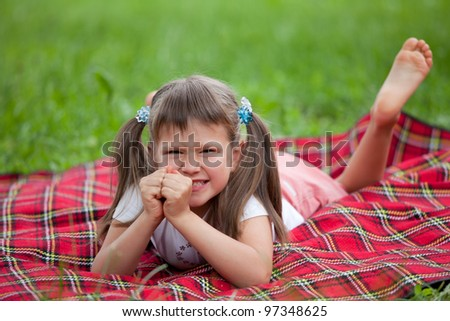 Little angry cute blond girl preschooler with ponytails lying on the red plaid on green grass in summer - stock photo