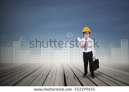 Little architect is holding a blueprint and bag outdoor - stock photo