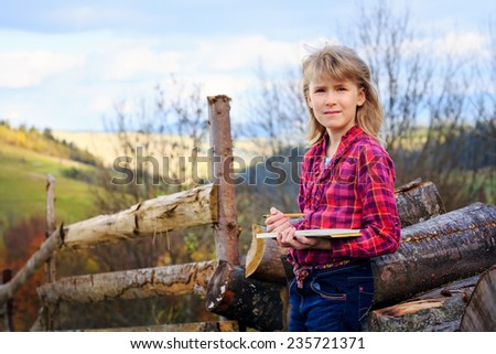 Little artist gril with sketch in note at autumn landscape - stock photo